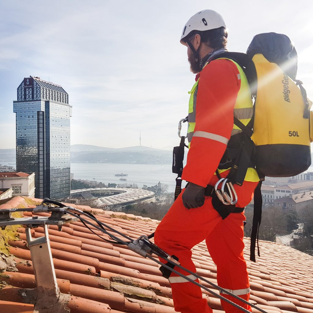 Man in high visibility clothing connected to roof anchor via twin leg safety fall arrest lanyards looking out at glass building