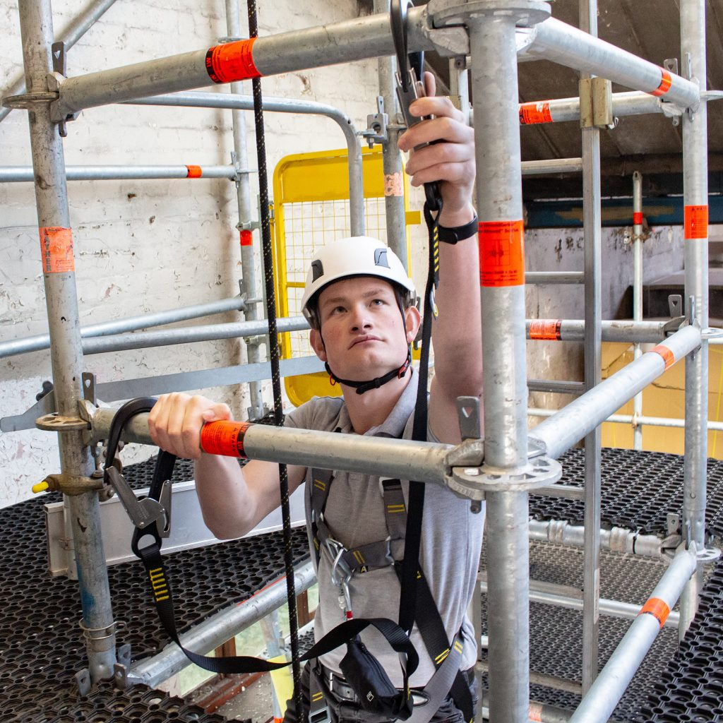 Man climbing scaffold using twin leg fall arrest lanyards with scaffold hooks