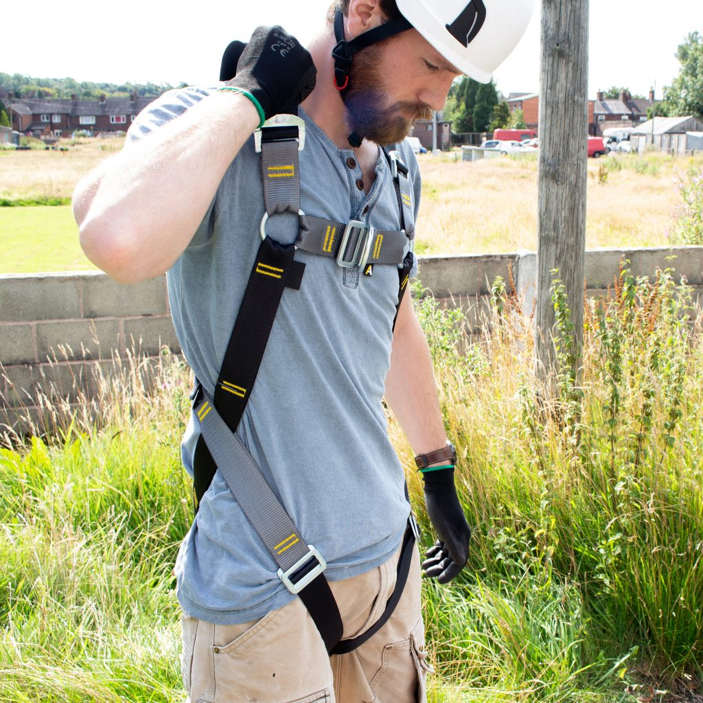 Man in safety harness adjusting size outdoor