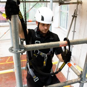 Black fall arrest safety lanyard in use whilst climbing scaffold structure